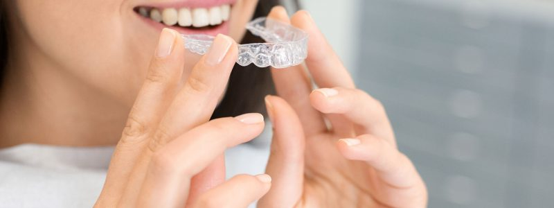 girl-holding-invisible-braces-moder-teeth-trainer-34XV875